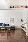 Gray upholstered sofa in a white living room with bookcase and high ceilings