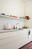 White fitted kitchen, with an open shelf holding colorful dishes
