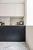 Fitted kitchen with a marble backsplash and a terrazzo floor