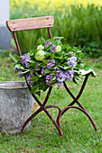 Bouquet of lilac and viburnum on chair in garden