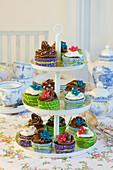 Cupcakes with colourful cuffs and sugar flowers on an etagere