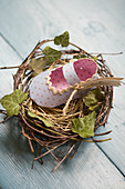 Homemade paper baby shoes in nests as place cards