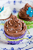 Cupcakes with chocolate frosting and silver dragees love beads in colorful cupcake liners