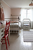 Old metal bed and floral wallpaper in vintage-style child's bedroom