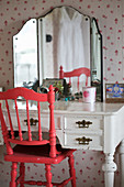 Red chair with turned spindles at old dressing table with triple mirror