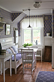 Scandinavian-style dining room with patterned wallpaper and wainscoting