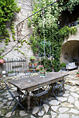 Old wooden table in a Mediterranean courtyard with natural stone floor
