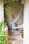 Metal bed with mosquito net on Mediterranean covered terrace