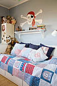 Skull and crossbones on wall above bed with patchwork quilt in child's bedroom