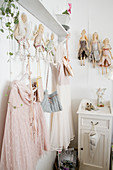 Romantic dresses and fabric dolls arranged on clothes rack