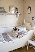 Old wooden sleigh bed in vintage-style child's bedroom with patterned wallpaper