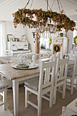 Wreath of dried flowers and chandelier above dining table