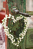 Heart-shaped wreath of lily-of-the-valley flowers hung from door handle