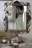 Woman in a vintage dress reflected in an ornate standing mirror