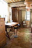 Swivel chair at the desk in the rustic living room with terracotta tiles