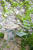 Rusty garden furniture in front of a natural stone wall with clematis