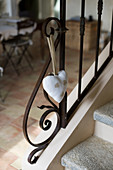 Fabric heart on ornate metal banister on stone staircase