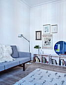 Classic sofa, floor lamp and shelves below works of art in the living room
