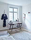 Klassikerstuhl und Schreibtisch vor Fenster, daneben Kimono an der Wand