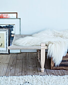 Day bed with animal fur, next to it pictures on wooden floorboard