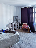 Bed, shelves and chair in bedroom with wooden floorboards