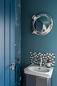 Mirror with porthole frame above sink in small blue bathroom