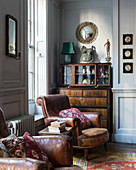Brown leather armchair in front of antique cabinet in living room