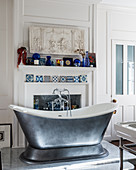 Silver free-standing bathtub in classic bathroom with mantelpiece