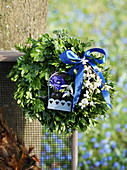 Boxwood wreath with a blue bow and flowers