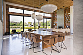 Upholstered chairs around dining table in large, open-plan interior with glass wall