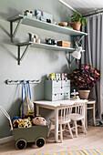 Tisch mit Stühlen, Puppenwagen und Regale im Kinderzimmer mit grüner Wand