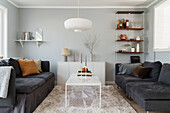 Sofa with scatter cushions and white coffee table in living room with light grey walls