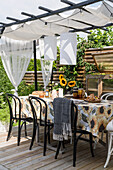 Dining table with chairs under pergola on terrace