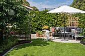 Sunny terrace with sitting area and parasol in the garden