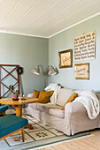 Living room with pale green walls and jumble sale decorations