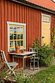 Seating area with old wooden table in front of the Swedish house with yellow window