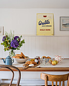 Old metal sign above a breakfast table with flowers on it