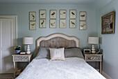 Bildergalerie mit Vogelbildern überm Bett im hellblauen Schlafzimmer