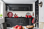 Red decoration as colour accent in grey-white kitchen with wall panel