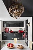 Kronleuchter überm Esstisch vor moderner Küchenzeile in Grau