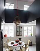 Kronleuchter überm Esstisch im modernen Wohnraum mit Galerie