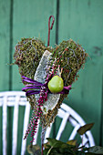 Homemade decorative plug: moss heart with budding heather, leaf of woolly zest, and green apples