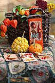 Herbstliche Dekoidee mit Karten, Zierkürbissen, Lampionblumen und Herbstlaub