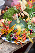 Round courgettes in a colourful autumn wreath of autumn leaves and berries
