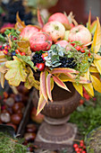 Apples in a colourful autumn wreath of autumn leaves and berries