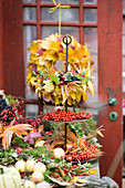 Etagere with autumn wreath of autumn leaves and berries