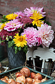 Autumn bouquet with dahlias, marigolds and stonecrop, tulip bulbs in a tin box