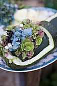Arrangement of hydrangea blossoms, privet berries, and snowberry in hollowed out Zucchini
