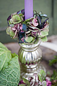 Candle with a wreath of hydrangea blossoms in a silver candlestick