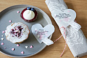 Stitched and inscribed hearts made of transparent paper with confetti